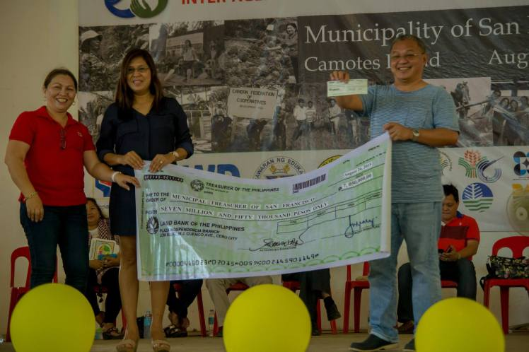 The Mayor and his wife receiving the cash support for the municipality.